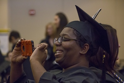 Photo of graduate holding a camera